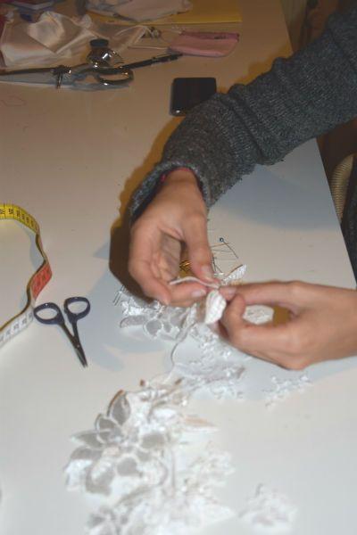 Sylvie découpe des motifs de dentelle de calais afin de les coudre un à un sur la robe de la mariée